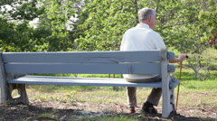 Portrait of Social Isolation - Senior Elderly Man Sitting Alone on Park Bench Stock Footage