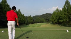 Japanese male golf player hitting tee shot Stock Footage