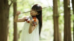 Attractive young Japanese girl playing violin in the woods Stock Footage