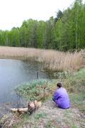 fisherman beside forest lake - stock photo