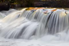 Waterfall photographed here with a long exposure, cascades over boulders Stock Photos