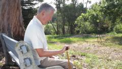 Portrait of Social Isolation - Lonely Senior Elderly Man Sitting on a Park Bench - stock footage