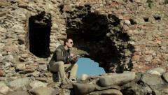 Modern guy sitting on old ruined tower, using tablet and enjoying in sunny day. Stock Footage