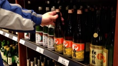 A hand takes bottles of Japanese wine from the shelf. Stock Footage