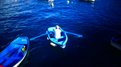 Fisherman peddle small boat Playa de Santiago La Gomera Canary islands Spain Stock Footage