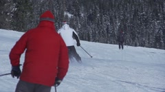 Skiers glide on snow track in slow motion Stock Footage
