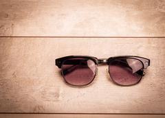 black sunglasses on wood floor - stock photo