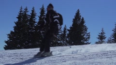 Two skiers pass in slow motion background with a forest of pines Stock Footage