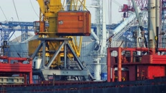 Close-up of working port crane with big bucket turns to load and unload cargo. - stock footage