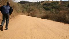 Young African child walking to school along winding rural dirt road Stock Footage