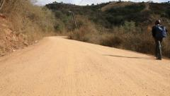 Young African scholar walking up rural dirt road to school Stock Footage