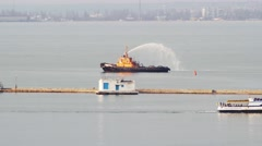 Tugboat sprays jets of water in harbor Stock Footage