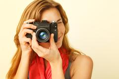 Young redhead woman looking through viewfinder with an old 35mm slr camera. Stock Photos