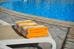 Two yellow striped towels lie on a sun-bed near a swimming pool - stock photo