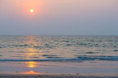 Setting orange sun and blue sea Stock Photos