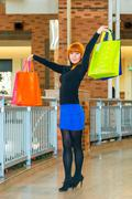 Girl in the mall with shopping bags shows Stock Photos