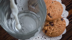 Pouring glass of milk, cookies Stock Footage