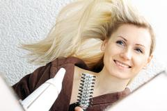 Happy young woman blow drying hair in bathroom Stock Photos