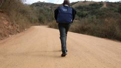 young African scholar walking to school along winding rural dirt road - stock footage
