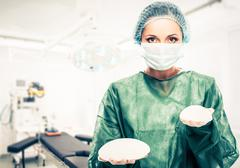 Plastic surgeon woman holding different size silicon breast implants in surge - stock photo