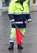 policeman with the red flag to signal the roadblock - stock photo
