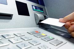 Insert card into ATM Stock Photos