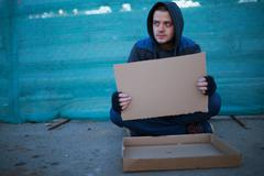 Homeless man holds blank cardboard for your text Stock Photos