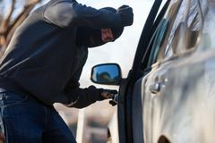 Thief stealing automobile car at daylight street in city Stock Photos