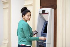 Asian lady using an automated teller machine - stock photo