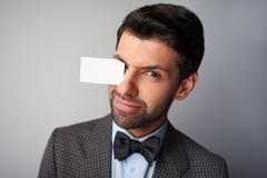Man winking and holding blank visiting card by eyebrow Stock Photos