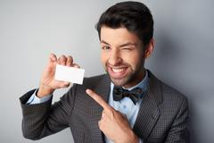 Smiling man pointing at blank visiting card and winking Stock Photos