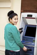 Asian lady using an automated teller machine Stock Photos