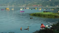 Lady washes clothes at lake,Pokhara,Nepal Stock Footage