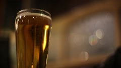 Pint glass of lager on pub table Stock Footage