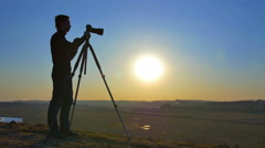 The photographer works near the tripod with camera by sunrise background - stock footage