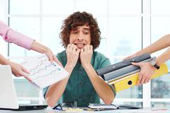 Stock Photo of Scared overworked young businessman with hands around him