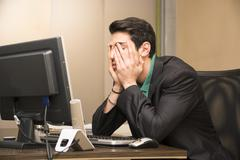 Tired bored young businessman in office Stock Photos