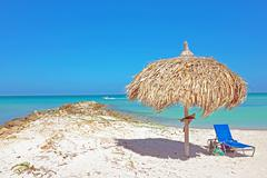 Grass umbrella at the beach on Aruba - stock photo