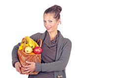 Beautiful woman coming from the market with a basket full of fruits - stock photo