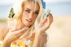 Pretty blond lady with colorful butterflies - stock photo