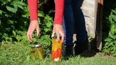 Girl carry out preserved food jars with vegetables from storage Stock Footage