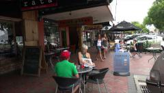 People sit at pavement cafe in Cambridge town centre, New Zealand Stock Footage