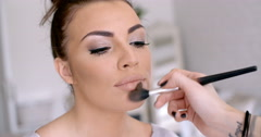 Makeup Artist Applying Lipstick to Pretty Woman - stock footage