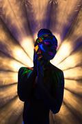 Sexy go-go dancer posing under ultraviolet light - stock photo