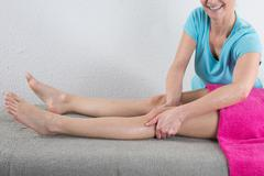 Beautiful young woman is ready for ankle's massage at  spa - stock photo