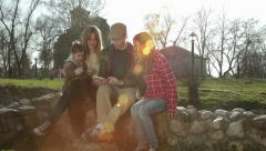 Happy family sitting on stone fence in the park and using tablet. Sunny day. Stock Footage