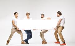 Casual clothed guys carrying huge billboard - stock photo