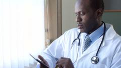 African American male doctor looking at tablet Stock Footage