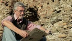 Elderly man pensioner sitting on bench and reading newspaper at stone fortress. Stock Footage