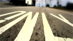 Low Angle Car POV of Painted Road Markings on Highway Exit Stock Footage